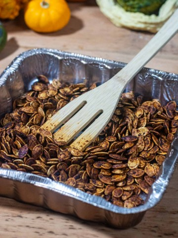 disposable aluminum pan filled with dark and smoked pumpkin seeds.