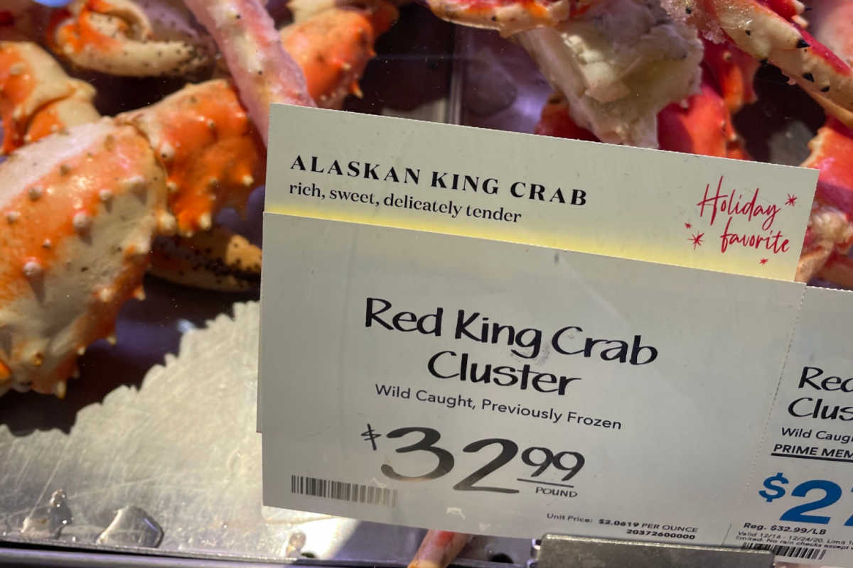 alaskan king crab clusters in the store's display with a price tag.