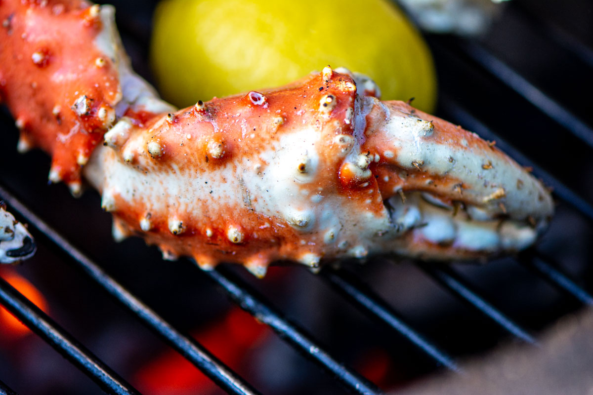 crab claw and lemon on the grill with the direct heat flames underneath.