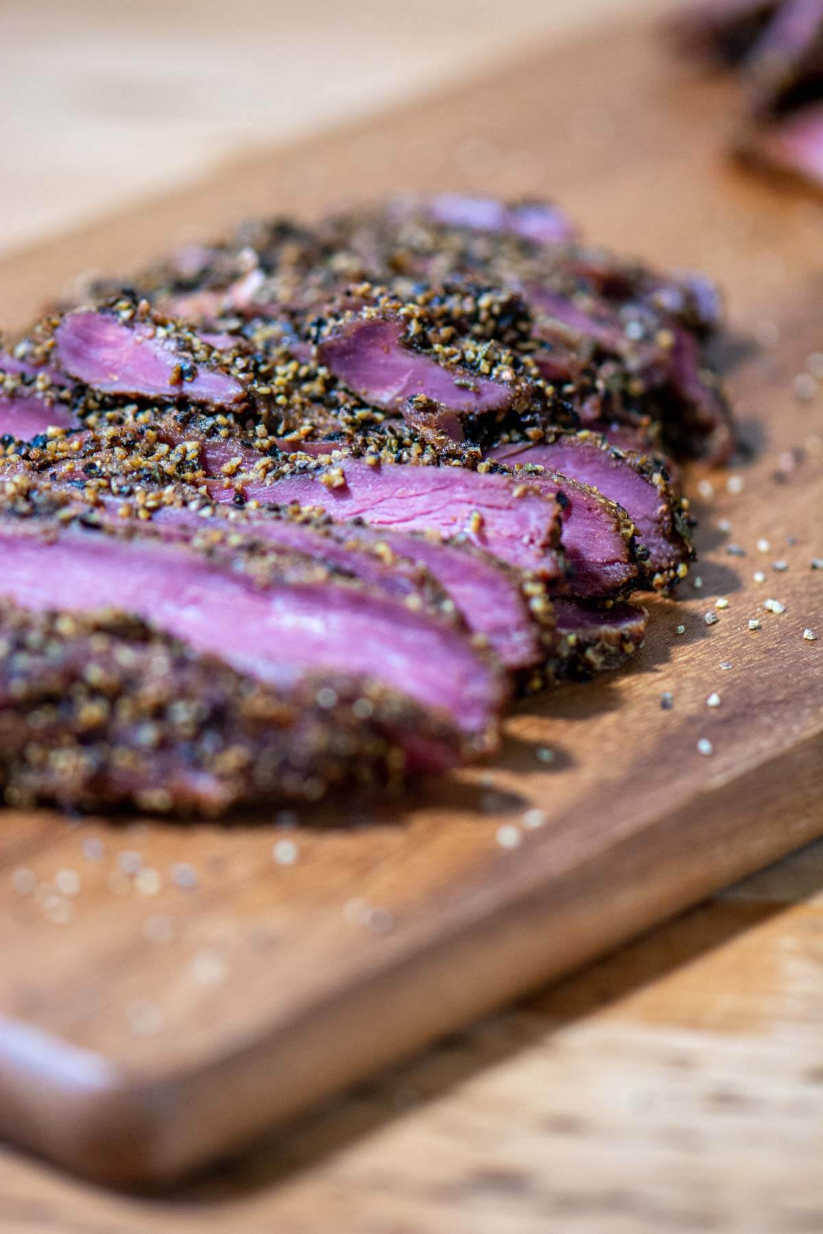 slices of goose breast on a cutting board coasted in the pastrami seasoning.