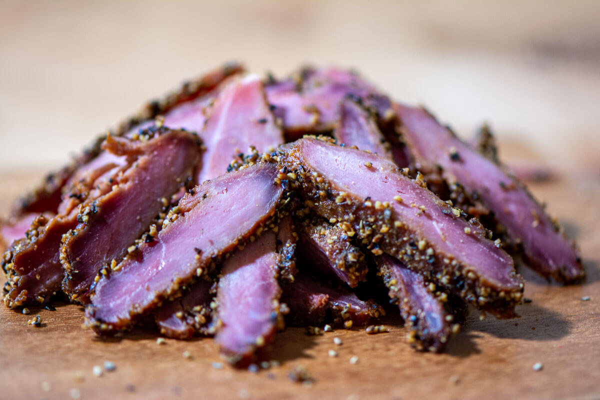 pile of cured and smoked pastrami with an insanely delicious crust.