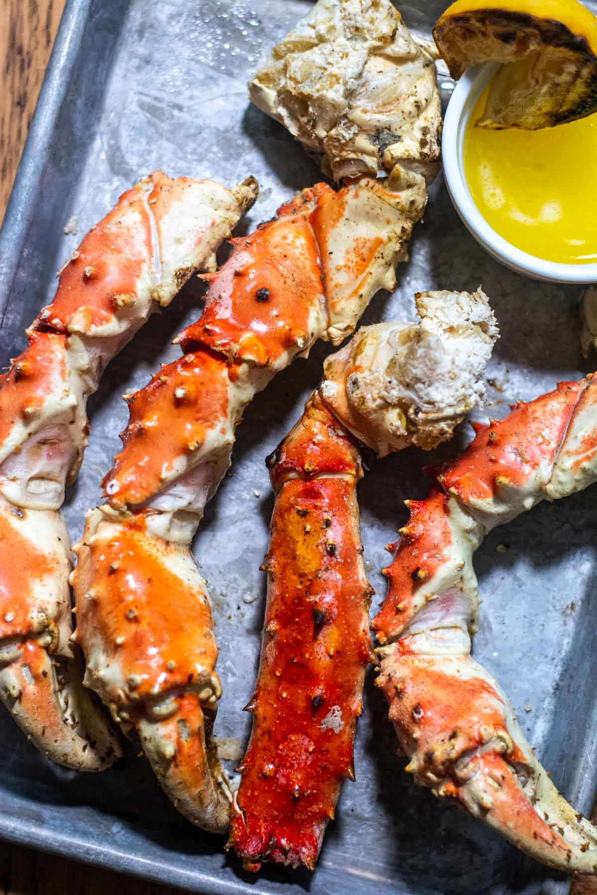 grilled crab legs on a serving tray and ready to be cracked open and dipped in butter.