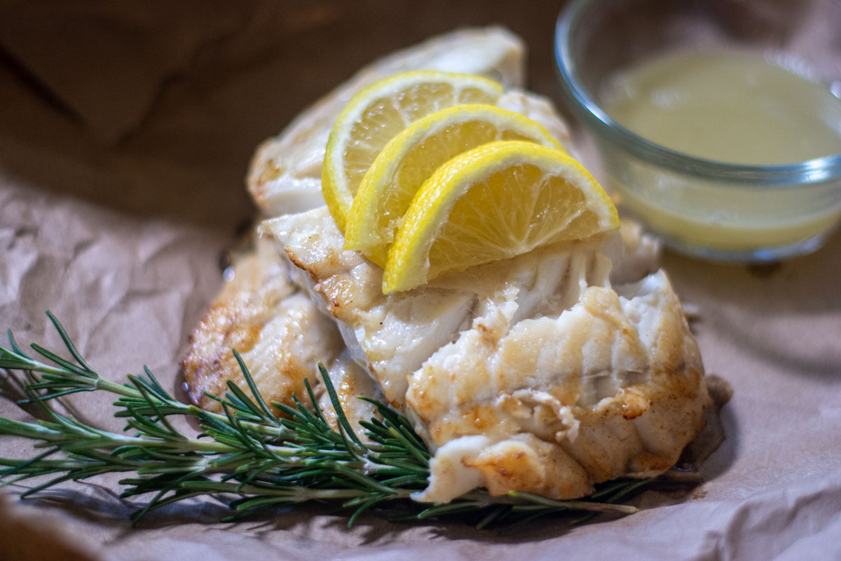 two fish fillets stacked on butcher paper with sliced lemons and rosemary.