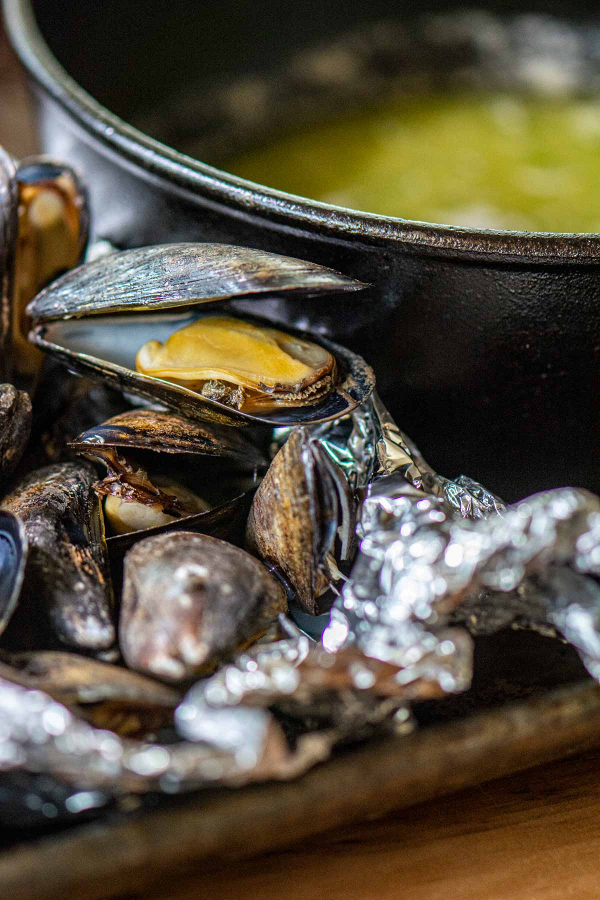 grilled mussels in a foil pack in front of melted butter.