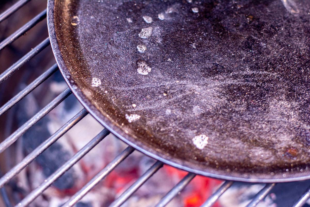 cast iron griddle being heated over direct flame and water drops sizzling.