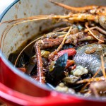 Seafood stew in a dutch oven loaded with fresh seafood.