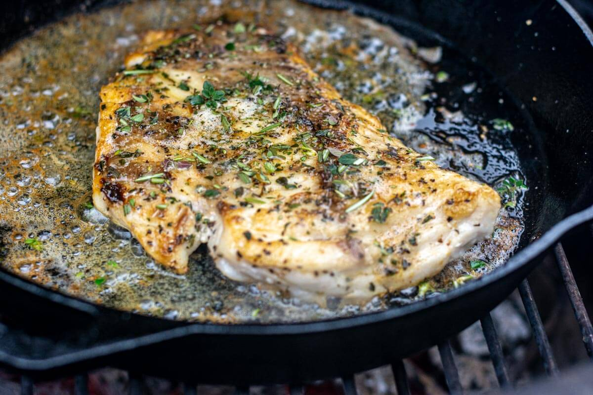 grilled rockfish in a cast iron skillet topped with herbs and brown butter.