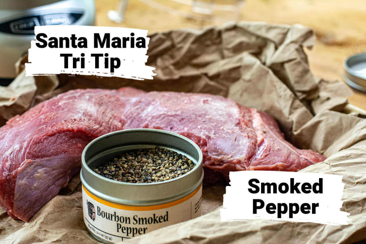 ingredients showing the trimmed tri tip and the bourbon smoked pepper on a butcher paper lined sheet pan.