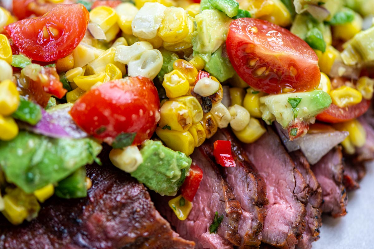 closeup of the sliced flank steak topped with the grilled corn and avocado salsa.