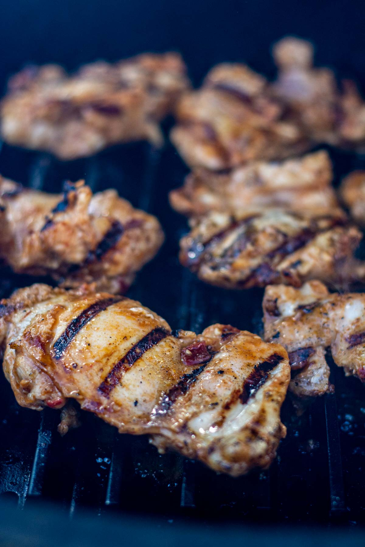 chicken thighs on the grill with distinctive sear marks.