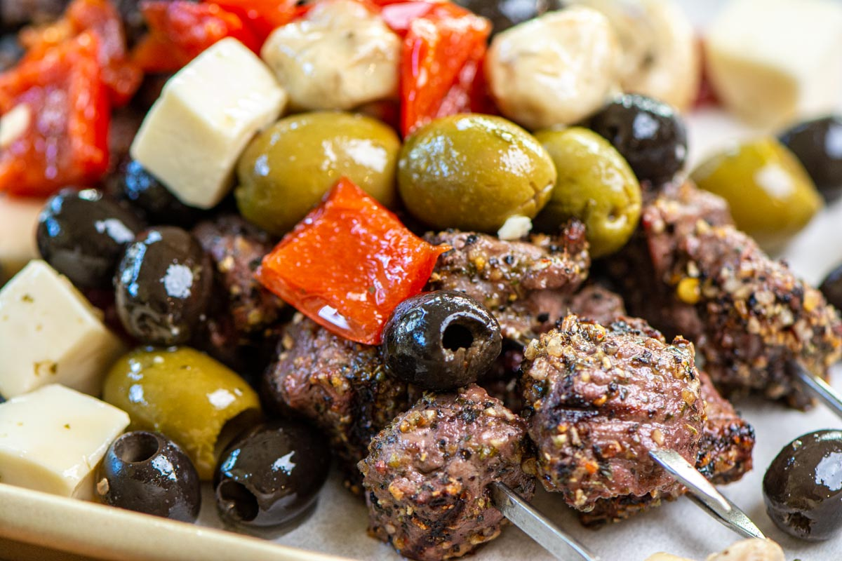 closeup of steak bites on skewers with greek seasoning and olives.