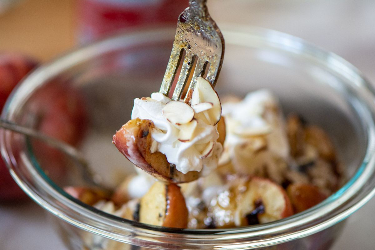 grilled apple slice on a fork with whipped cream and almond slivers.