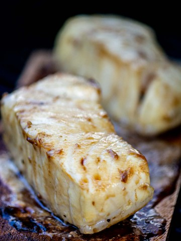 two filets of sea bass on a cedar plank on the grill with a light bourbon glaze.