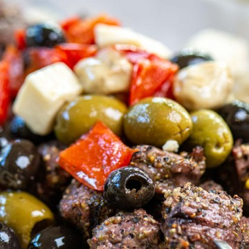 grilled steak bites on metal skewers topped with a greek olive salad mix.