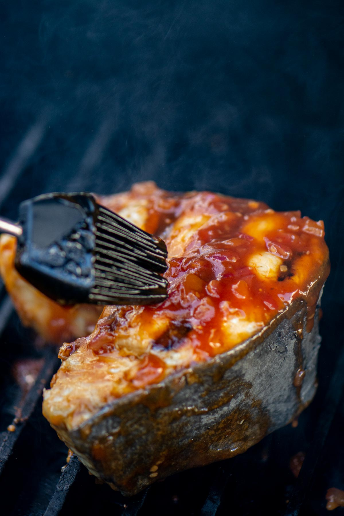 brushing on a homemade sweet and sour sauce on the grilled shark steak.