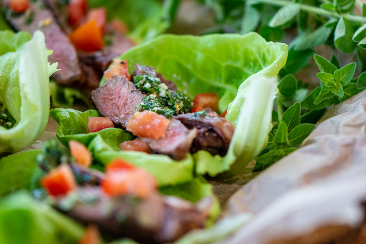 closeup of a lettuce wrap filled with grilled sirloin and a homemade Chimichurri sauce.