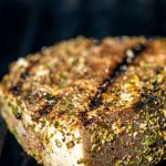 swordfish steak on the grill grate with sear marks and coated in a homemade jerk seasoning rub.