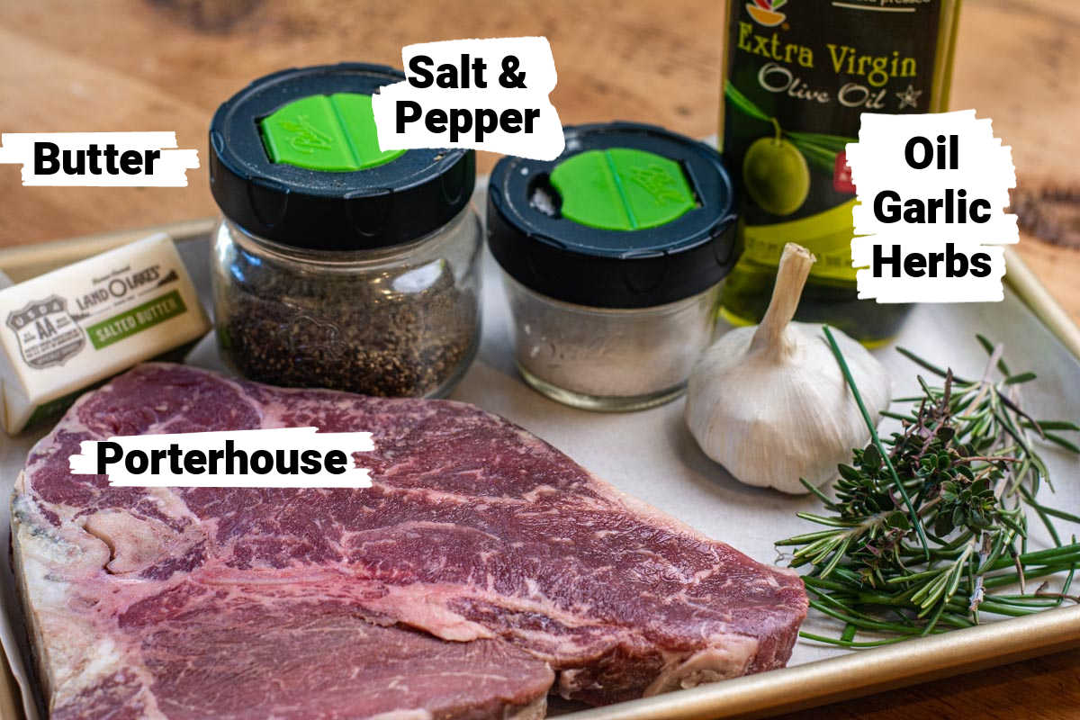 ingredients for the porterhouse with her butter on a sheet pan with labels.