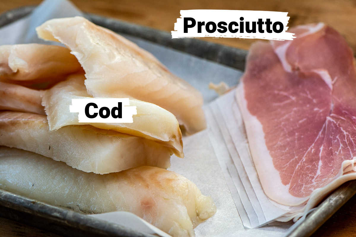 Ingredient photo with cod fillets and prosciutto on a lined sheet pan with labels.
