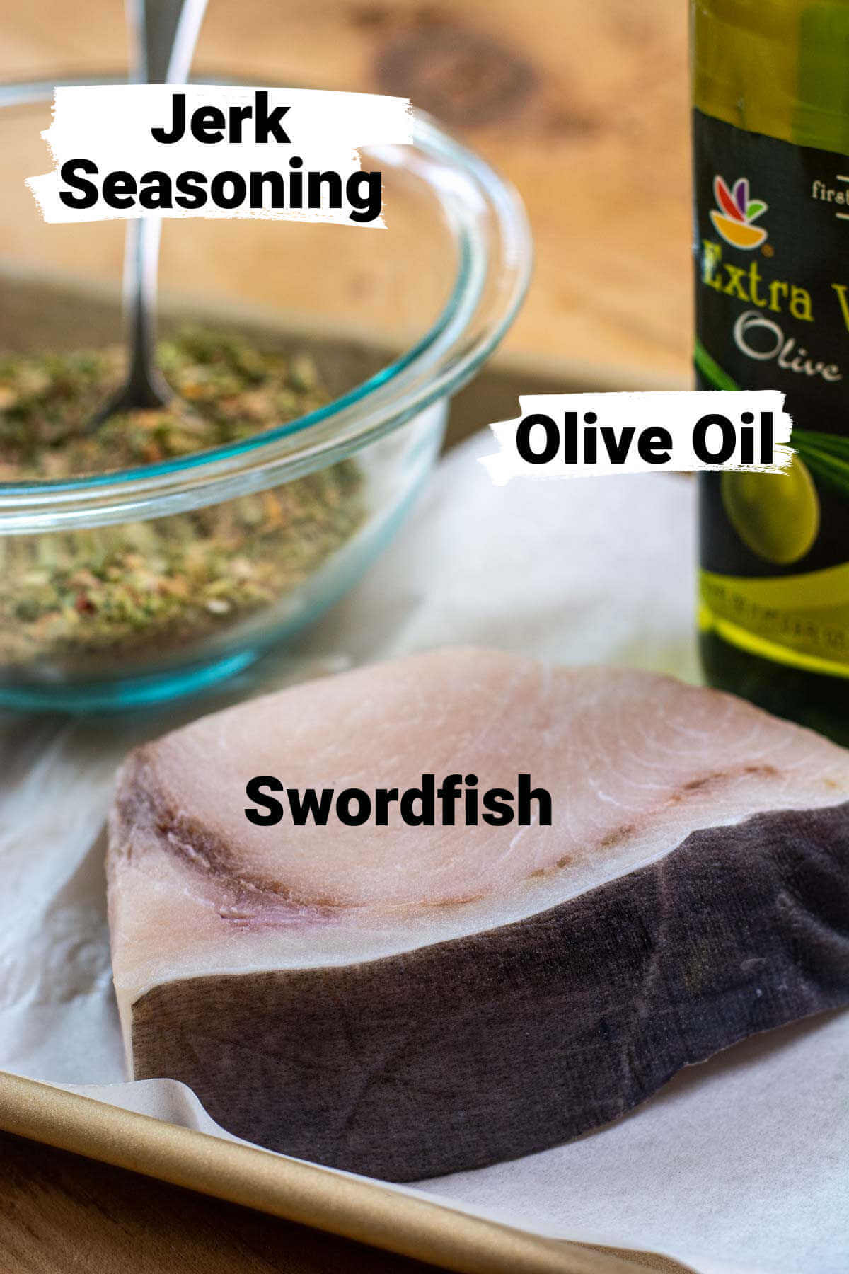 sheet pan with swordfish, olive oil and seasoning on a lined sheet pan.