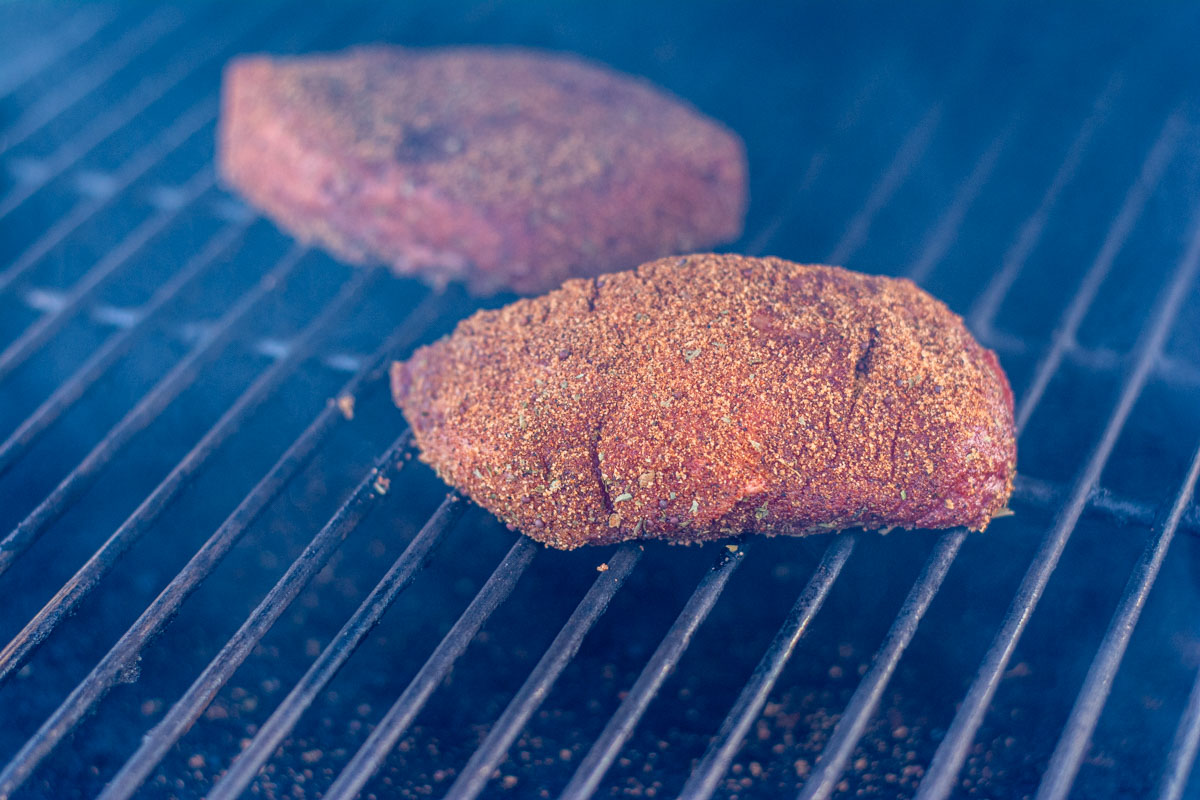 well seasoned top round steak on the grill with lots of smoke billowing.