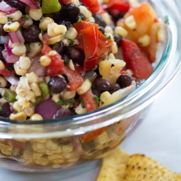 grilled corn and black bean salsa packed with fresh vegetables in a bowl and corn chips on the table.