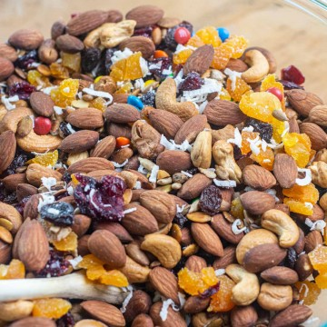 glass bowl with wooden spoon and mixed smoked trail mix ready to bag and serve.