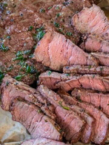 closeup of the sliced bison sirloin with herb butter.