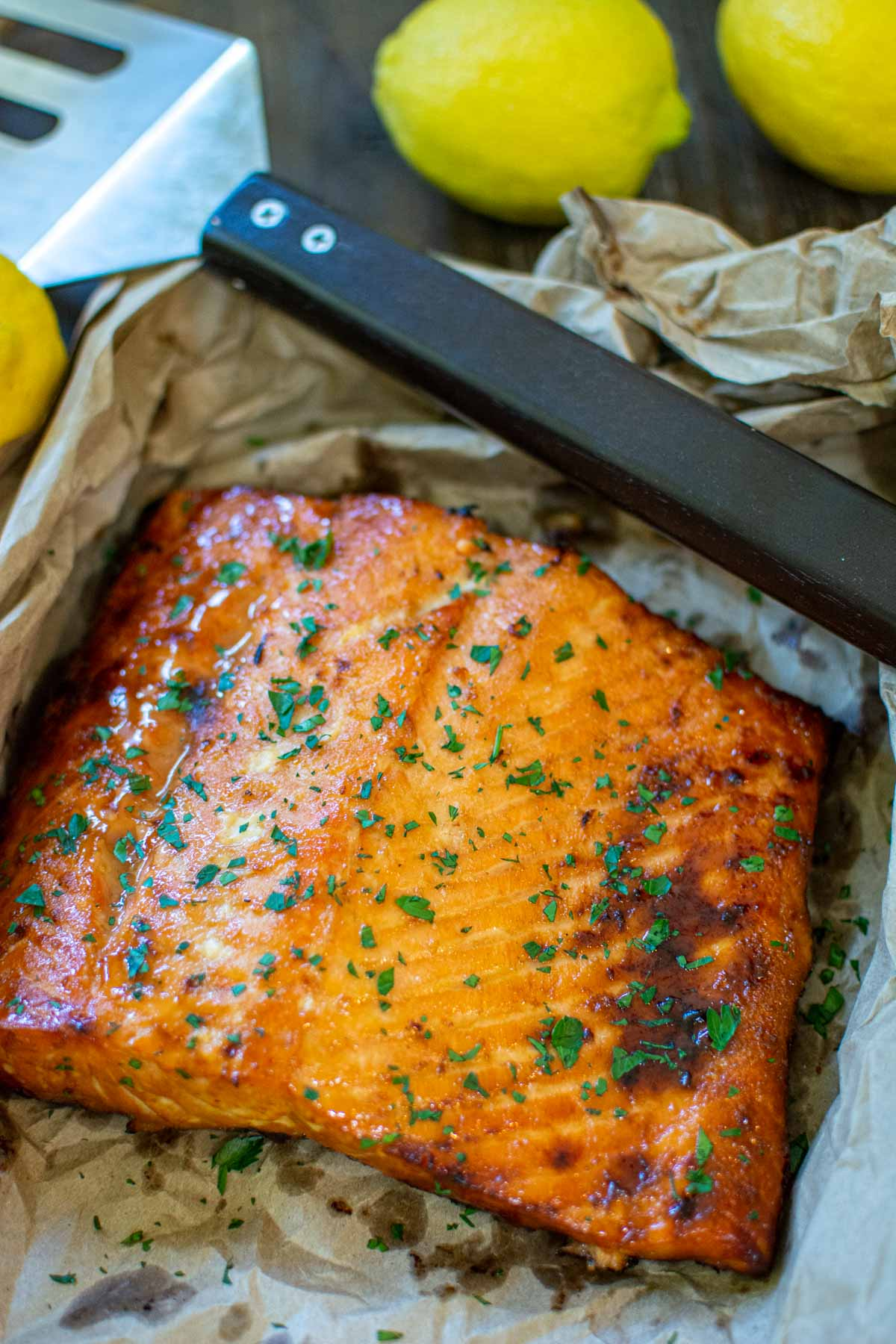 salmon on a sheet pan after grilling with lemons in the background.