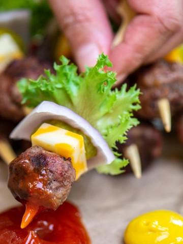 woman dipping the meatball cheeseburger kabob in ketchup and mustard.