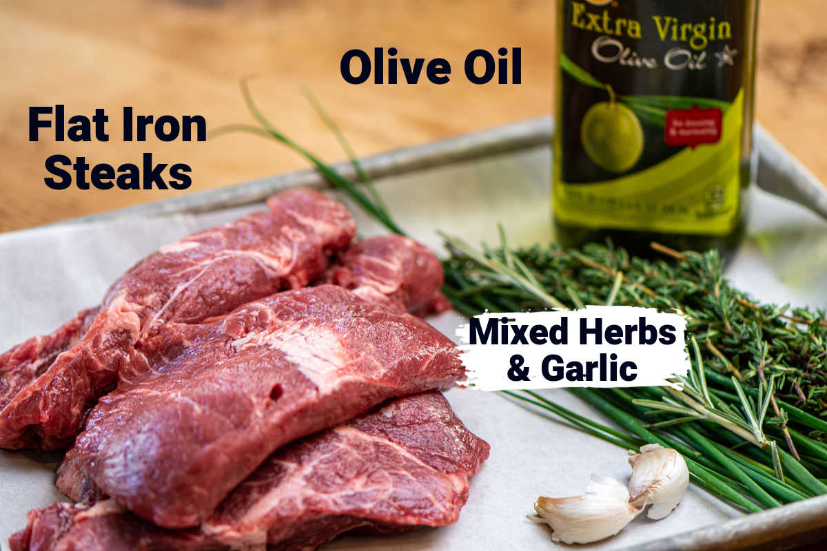 ingredient photo showing flat iron steaks, mixed fresh herbs, garlic and extra virgin olive oil on a lined sheet pan.