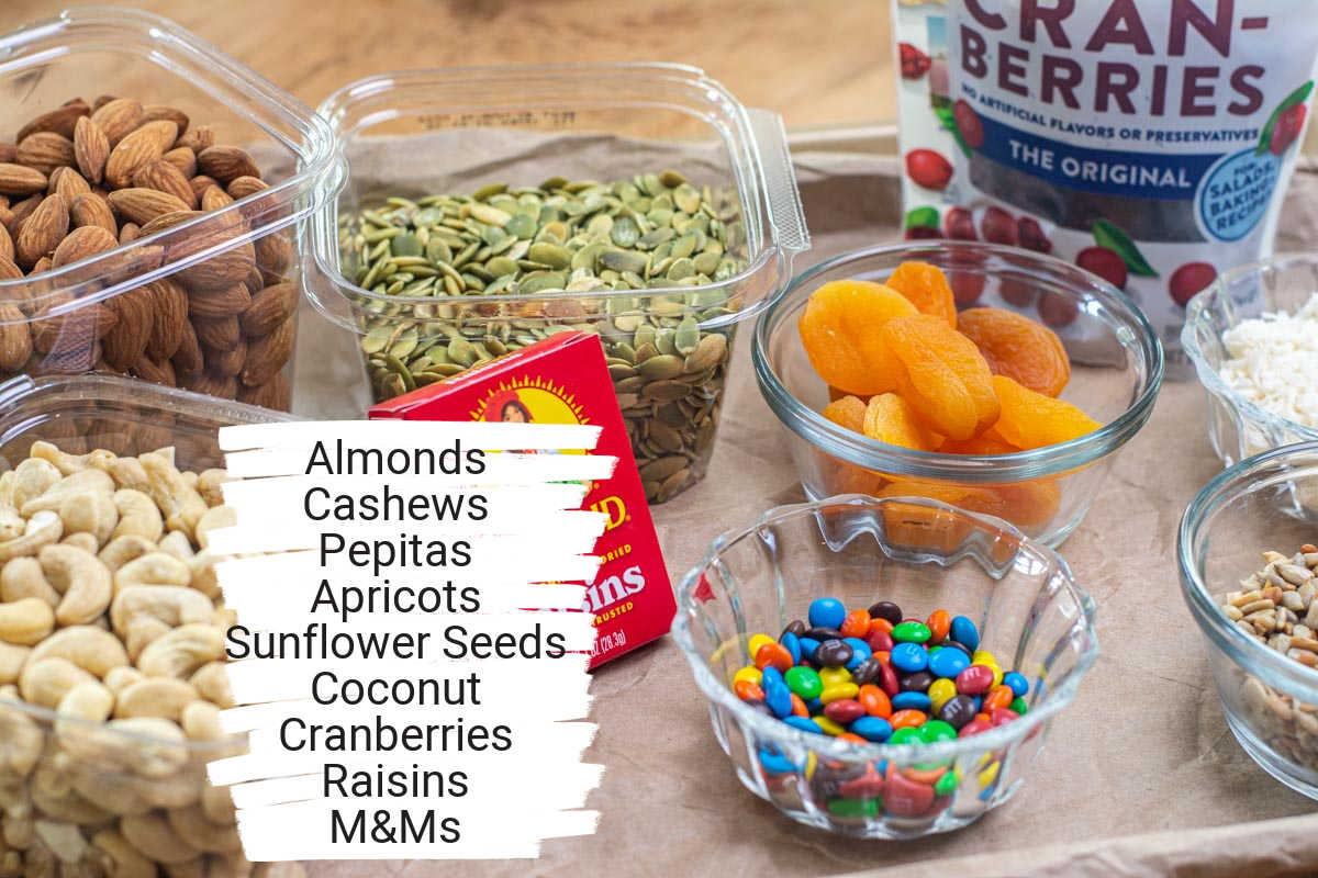 ingredient photo showing all the seeds, nuts, fruit and chocolate on a lined serving tray with labels.