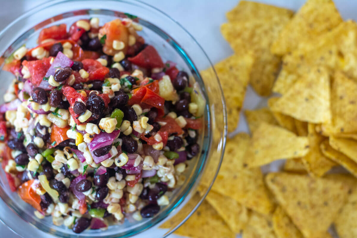 top down view of bowl of grilled corn and black bean salsa with chips on the table.