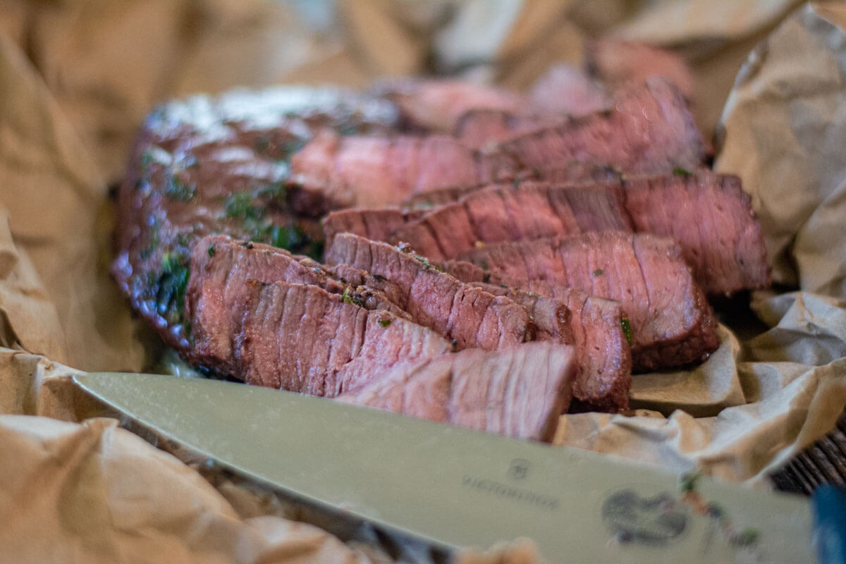 thinly sliced bison steaks on a butcher paper lined sheet pan with a knife.