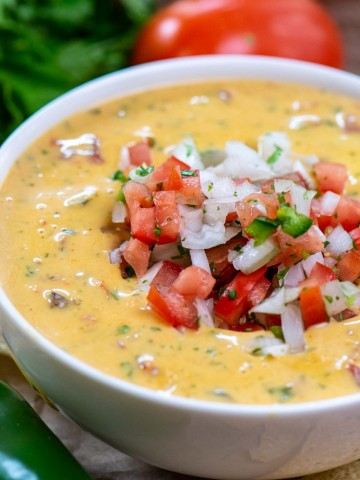 bowl of queso topped with fresh chopped vegetables and tomatoes, cilantro and jalapeño on the table.