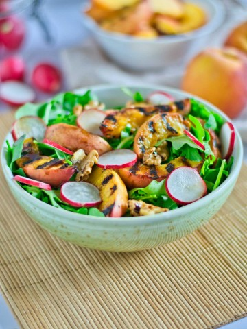 bowl of grilled peaches on a bed of lettuce and topped with radishes and fresh cracked walnuts.