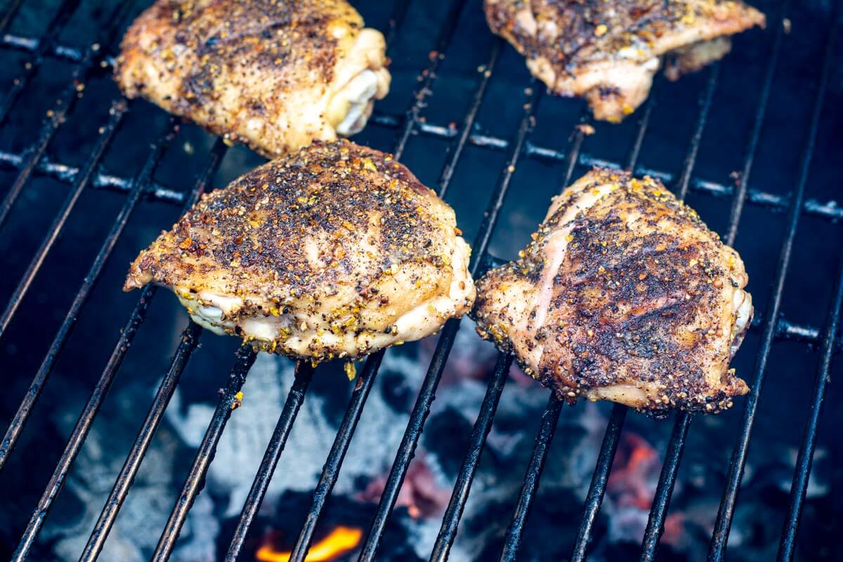 four chicken thighs over direct heat on the grill grate with flames underneath.
