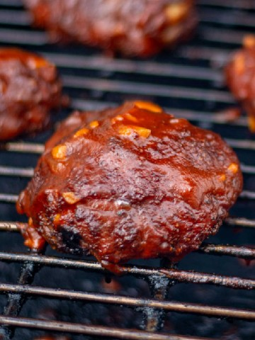 smoked chicken thigh on the grill covered in a thick BBQ sauce.