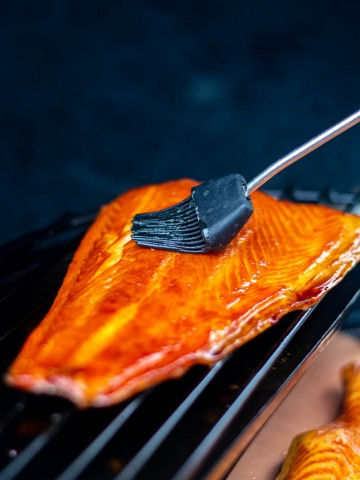 brushing on honey on the salmon as it is being smoked on the grill.