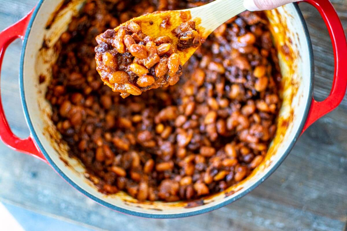 top down view of wooden spoon holding thickened baked beans over the red cooking dish.