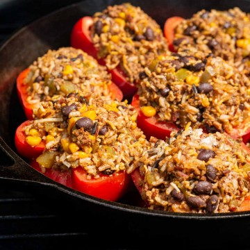 skillet on the grill filled with stuffed peppers with mexican seasoning.