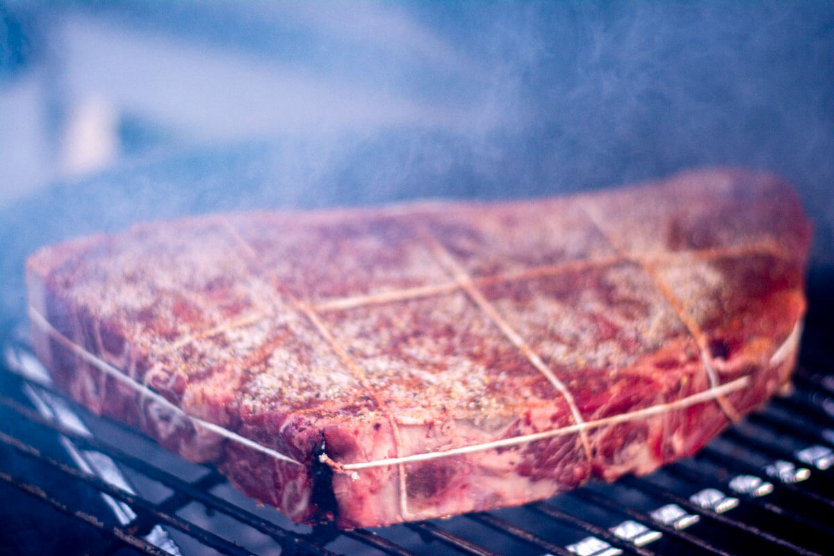 seasoned chuck roast on the grill with a drip pan under the grate and smoke billowing around.