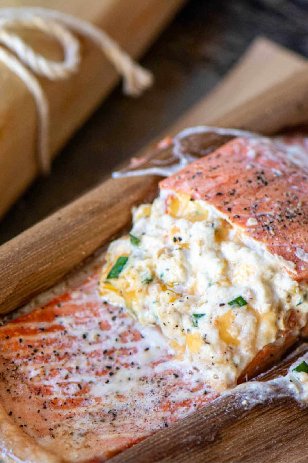 salmon filled with cream cheese inside a cedar wrap after being grilled.