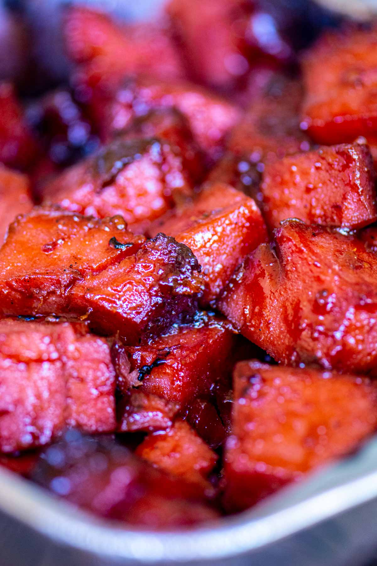 disposable pan on the grill filled with smoked bologna burnt ends.