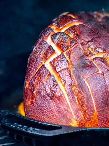 half a ham on a bed of orange slices being smoked on the grill and the score marks are opening up.
