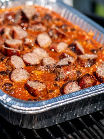 disposable pan filled with beer brat chili on the grill.