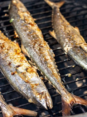 grilled whole Spanish Mackerel stuffed with Garlic on the Grill.