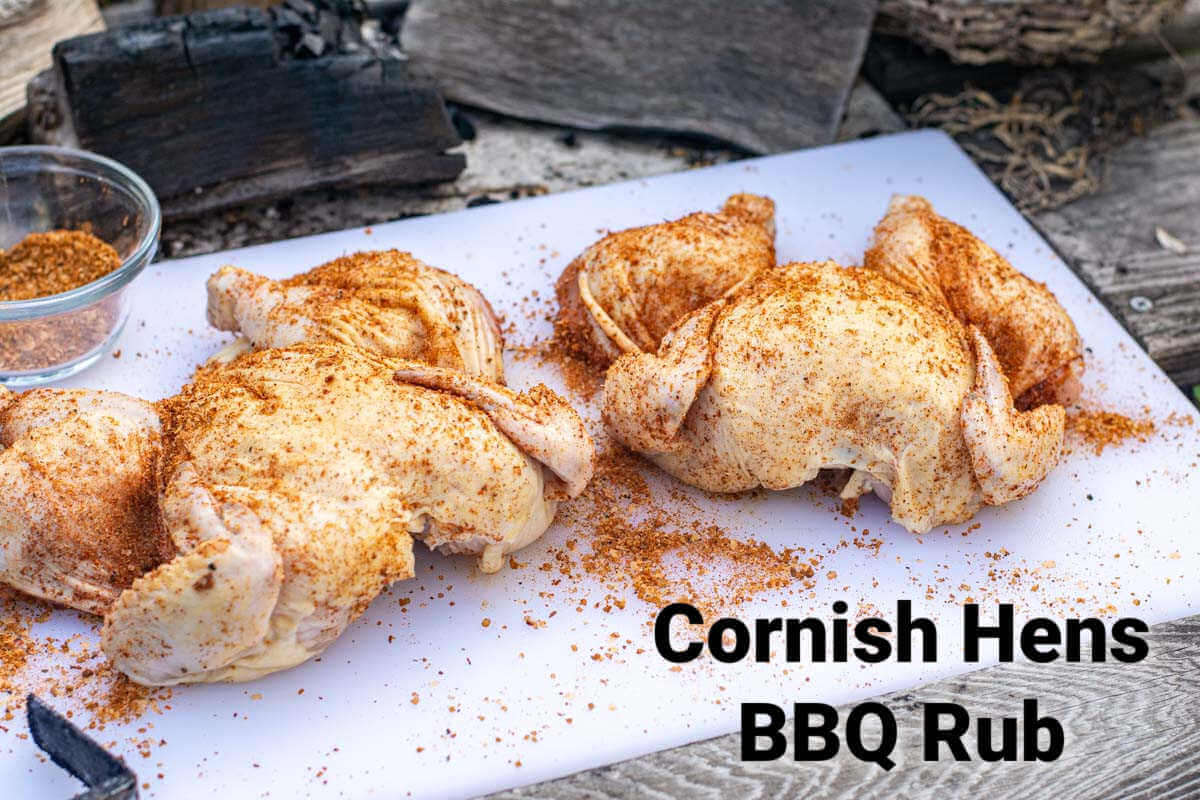 two cornish hens butterflied on a cutting board with BBQ rub and labels for the ingredients.