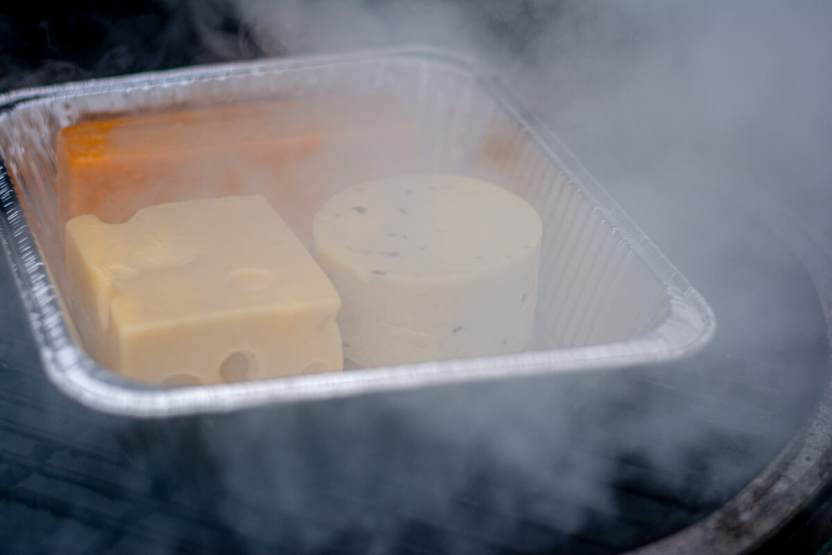 disposable pan with several hard cheeses on the grill with billowing smoke.