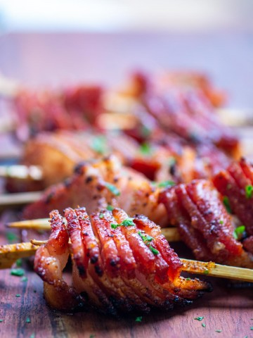grilled bacon skewers on a cutting board and ready to be served.